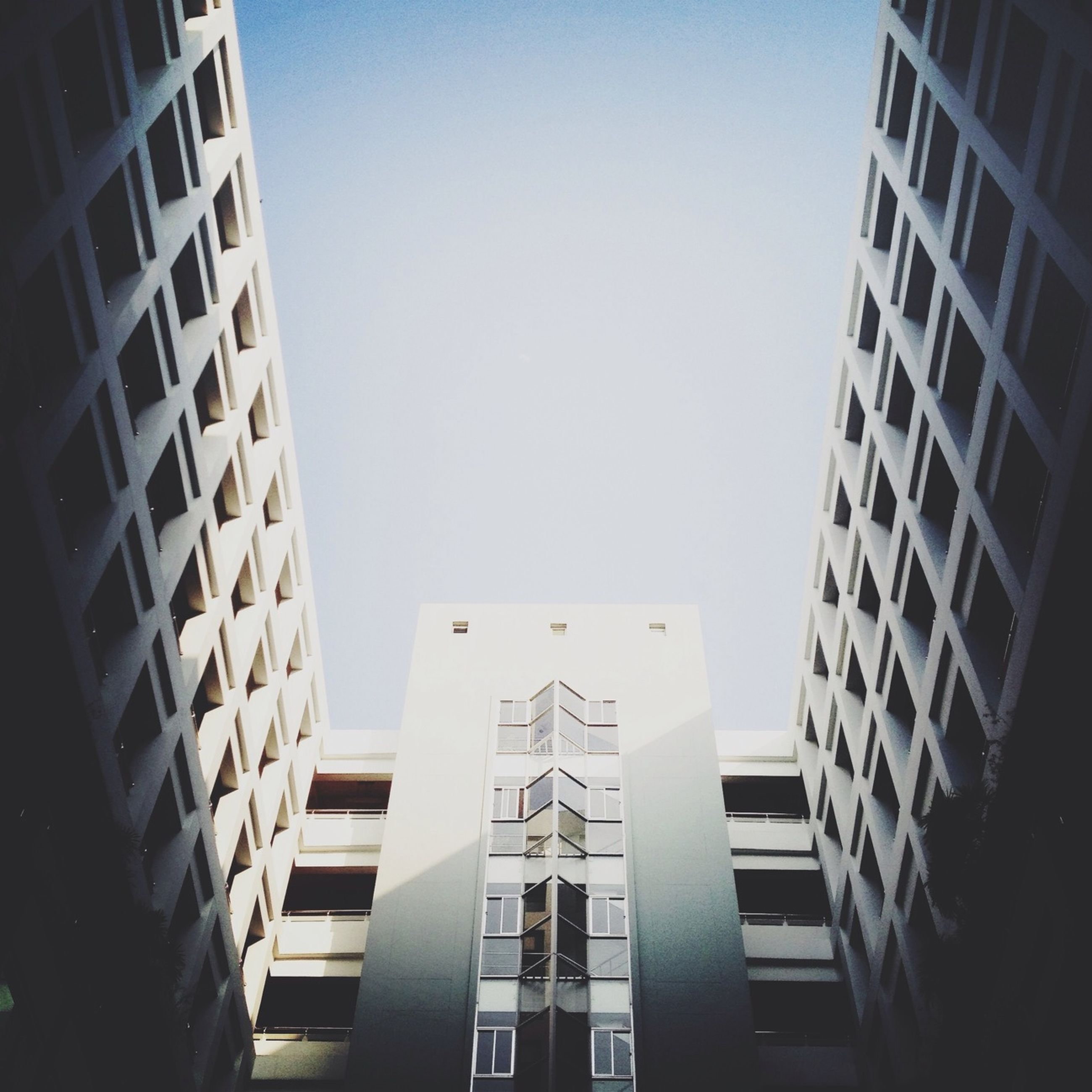 architecture, built structure, building exterior, low angle view, clear sky, window, modern, building, office building, city, glass - material, copy space, tall - high, day, sky, outdoors, no people, tower, blue, skyscraper