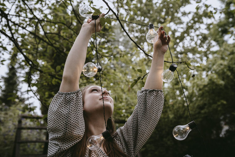 Portrait of woman with bubble against trees