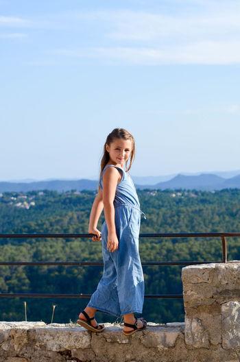 Portrait of girl standing on mountain against sky