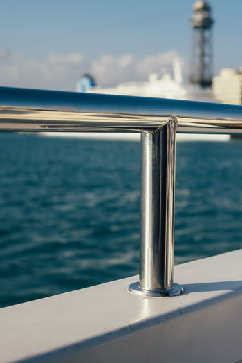 A closeup shot of a silver ship railing with Barcelona and the sea in the background. Blue Boat Close-up Marine Nautical Railing Sailboat Sailing Sea Selective Focus Ship Silver  Water