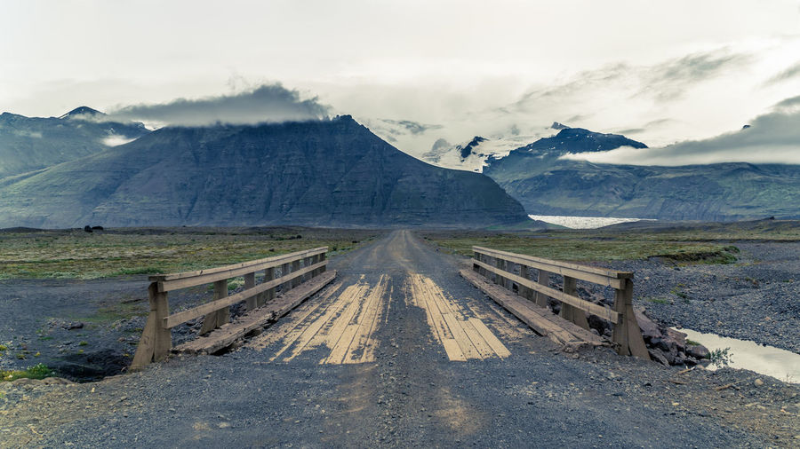 An old wooden bridge on a road to icelandic mountains covered in clouds Bridge Connection Day Environment Landscape Mountain Nature No People Outdoors Scenics Sky The Great Outdoors - 2017 EyeEm Awards