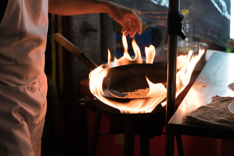 Appliance Burning Chef Fire Fire - Natural Phenomenon Flame Food Food And Drink Hand Heat - Temperature Holding Human Body Part Human Hand Kitchen Utensil Midsection Occupation People Preparation  Preparing Food Real People Skill  Working