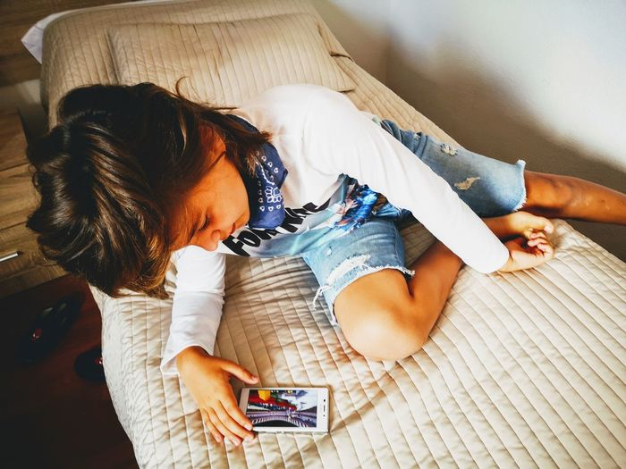 High angle view of girl using mobile phone at home