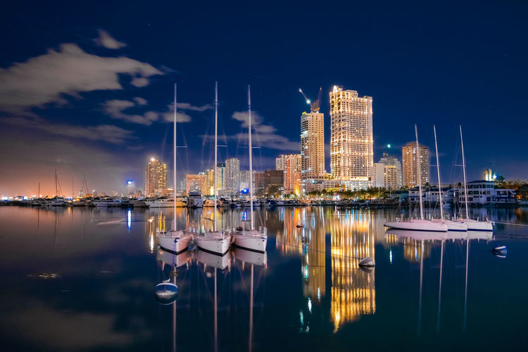 Sailboats in harbor by buildings against sky at night