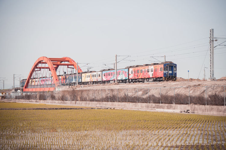 Train on field against clear sky