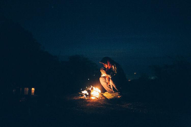 Man crouching by campfire at night