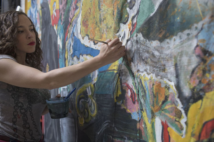 Midsection of woman holding multi colored graffiti on wall
