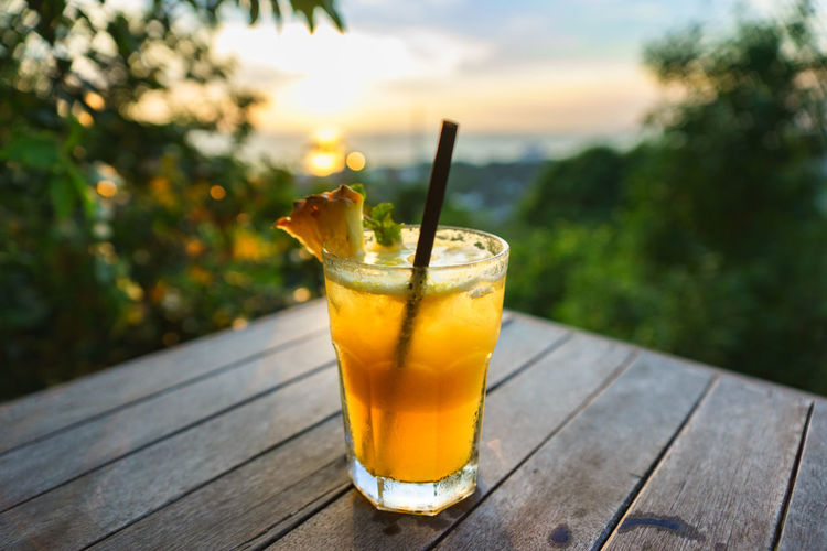 Close-Up Of Drink On Table During Sunset