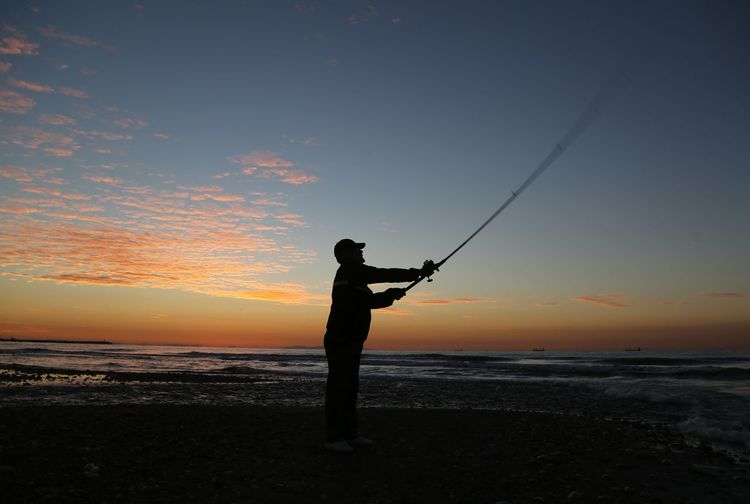 Fisherman Sky Sunset Water Sea Fishing Real People Land Beauty In Nature Silhouette Scenics - Nature Rod Fishing Rod Beach One Person Horizon Over Water Activity Holding Nature Lifestyles Outdoors