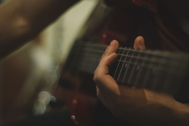 50mm Canon Close-up Showcase April Focus On Foreground Guitar Holding Human Finger Indoors  Instrument Leisure Activity Lifestyles Men Music Music Musical Instrument Musical Instruments Musician Part Of Person Playing Playing Guitar Selective Focus Strings Unrecognizable Person