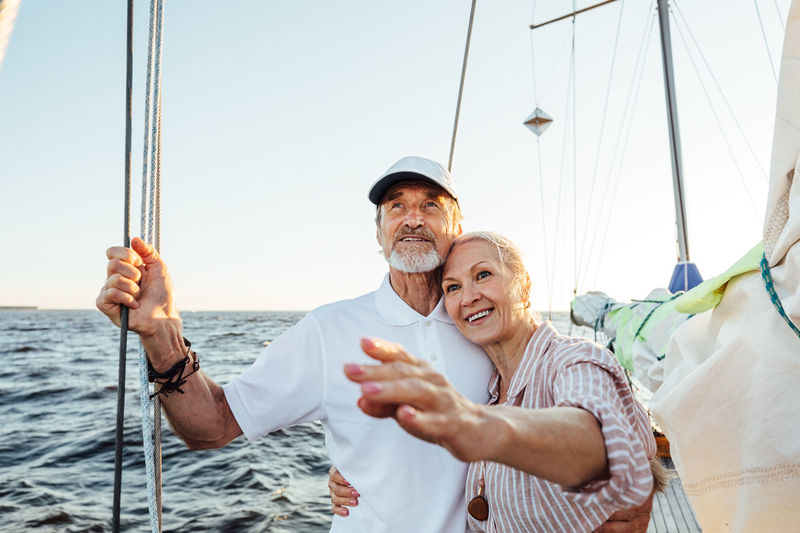 Smiling senior couple on sailboat in sea against sky