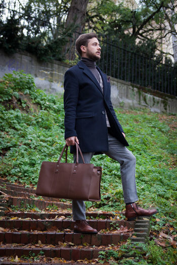 Full length of thoughtful businessman holding bag while standing outdoors