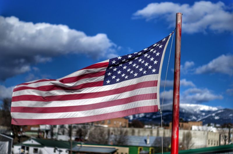 Close-up of american flag waving against blue sky during sunny day