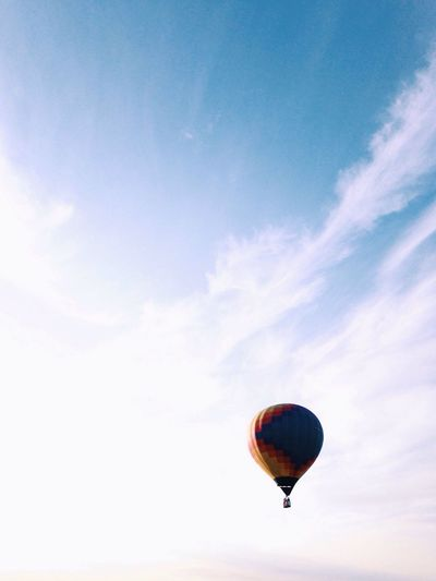 Hot air balloon flying against sky during sunset