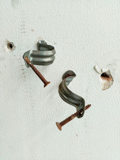 Rusty nails with brackets on white wall