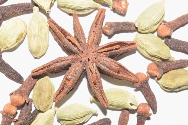 Close-up of star anise and cardamoms against white background