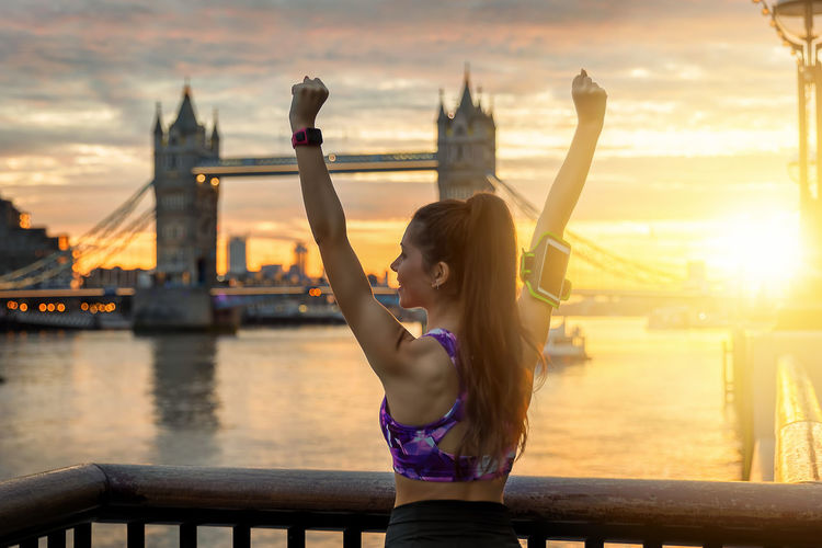 Rear View Of Woman In Sports Clothes With Arms Raised In City During Sunset