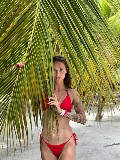 Portrait of woman in bikini standing by palm tree