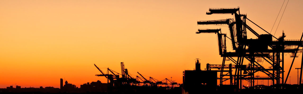 Silhouetted cranes against sky at sunset