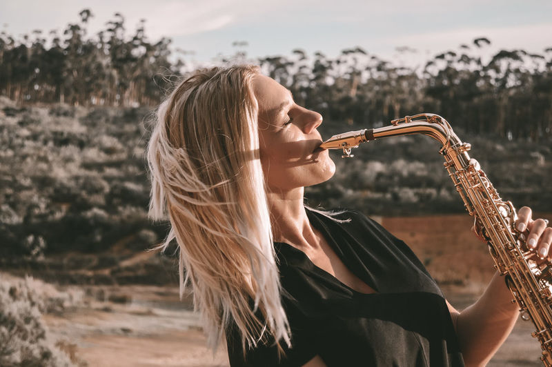 Beautiful woman playing saxophone against tree