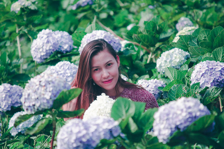 Portrait of woman with pink flowers in garden