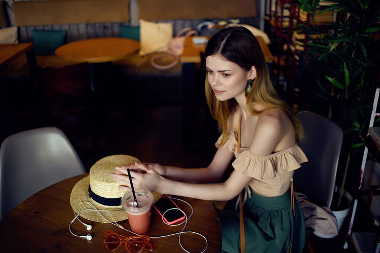 Young woman holding drink at table