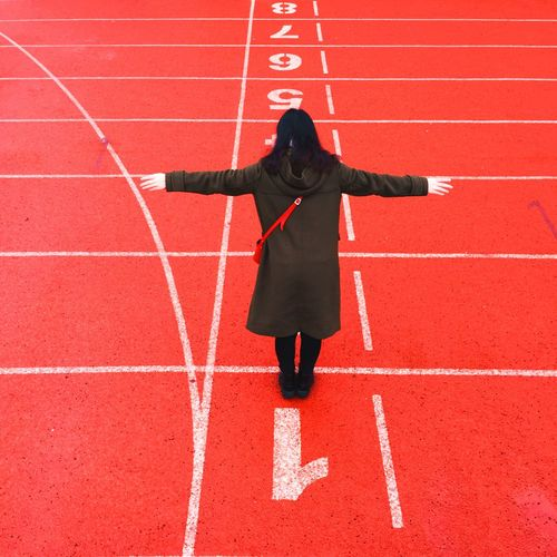 Full Length Of Woman With Arms Outstretched Standing On Running Track