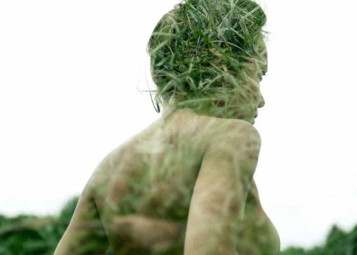 Double Exposure Of Woman And Grass Against Clear Sky
