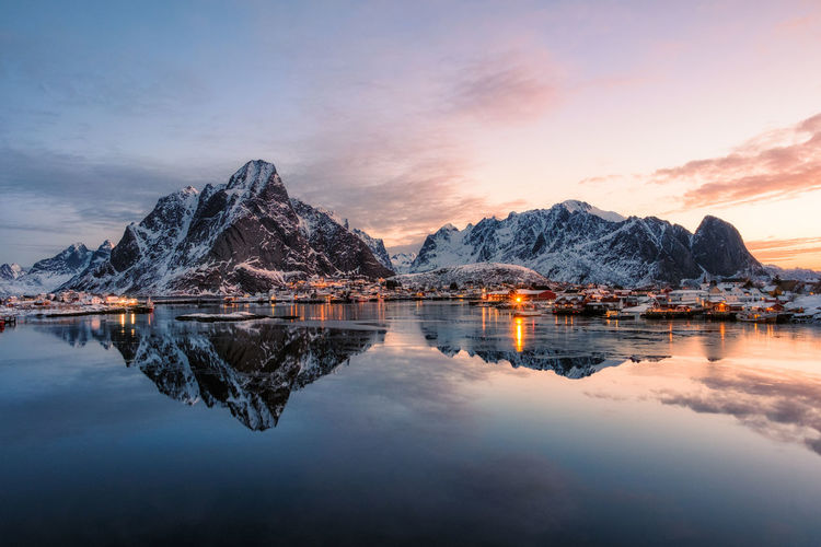 Fishing village with snow mountain at sunrise in Reine, Lofoten, Norway Water Sky Mountain Reflection Mountain Range Cloud - Sky Tranquility Scenics - Nature Beauty In Nature Tranquil Scene Lake Nature No People Dusk Sunset Waterfront Idyllic Rock Winter Snowcapped Mountain Mountain Peak
