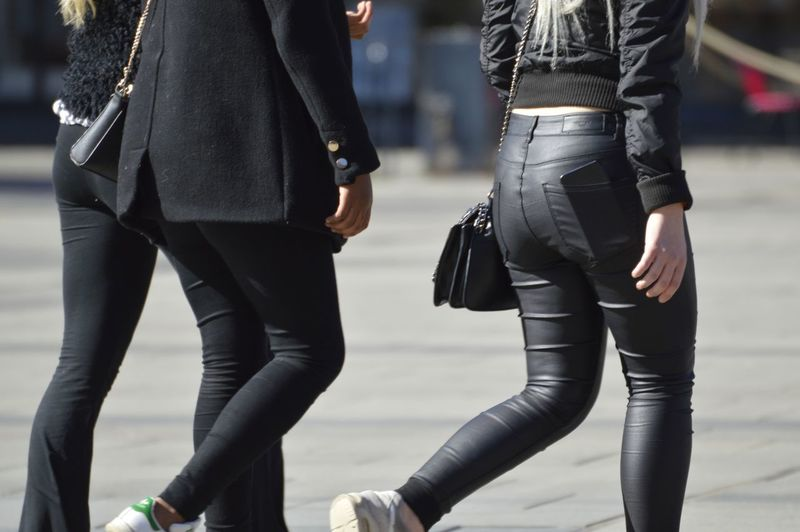 Midsection of friends walking on street