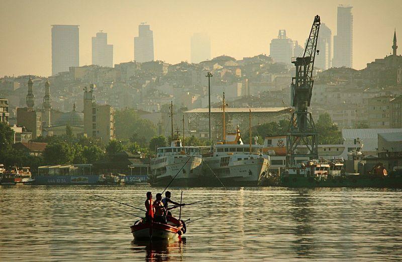 Men fishing in bosphorus against city