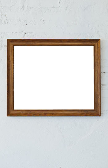 Wooden photo frame on the white room wall inside the building