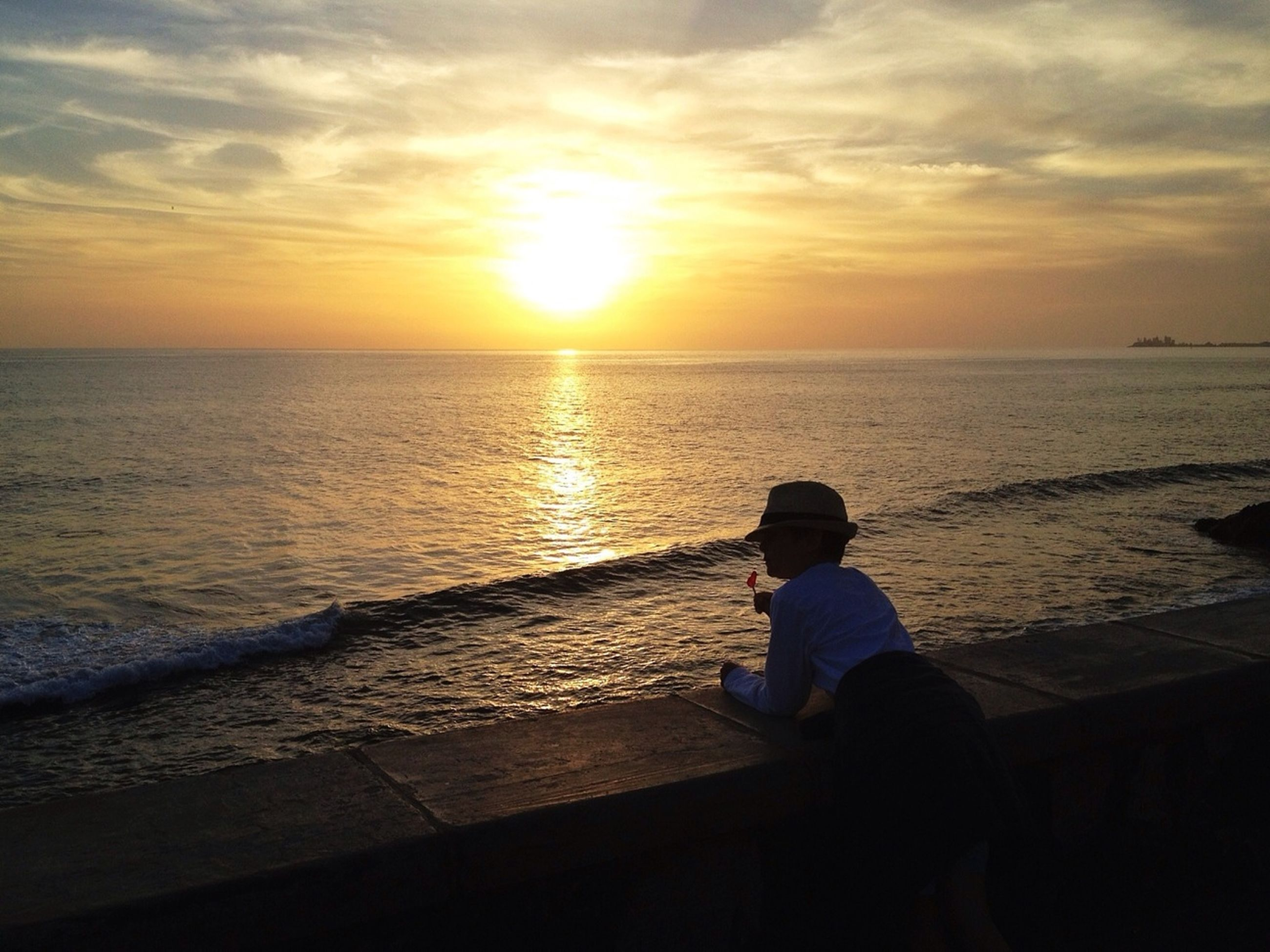 sunset, sea, horizon over water, water, sky, sun, scenics, lifestyles, leisure activity, beauty in nature, tranquil scene, beach, tranquility, orange color, idyllic, standing, silhouette, nature