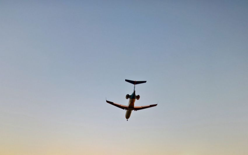 Low angle view of silhouette airplane against clear sky