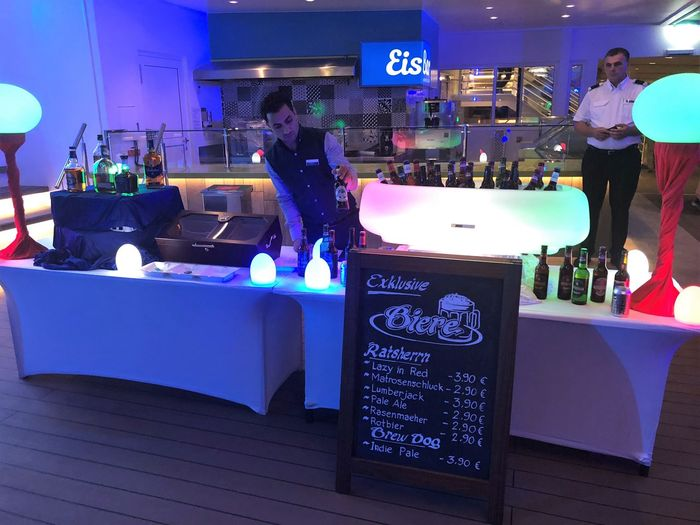 Group Of People Men Bar - Drink Establishment Illuminated Night Adult Real People Communication Food And Drink Text Lifestyles Women Leisure Activity Indoors  People Business Restaurant Drink Crowd Nightlife Bar Counter Dekoration Bar Getränke TUI-Cruises