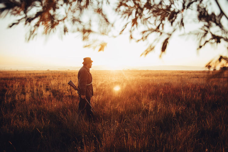 Agriculture Field Grass Gun Hunter Hunting Leisure Activity Lifestyle Man Mature Meat Nature Outdoors People Pointing Prey Rural Scene Skill  Sniper Sunflare Sunrise Sunset Tranquility Weapon