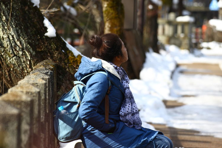 Portrait of an asian woman in a park with snow Adult Architecture Backpack Casual Clothing Clothing Day Females Focus On Foreground Hairstyle Hood - Clothing Leisure Activity Lifestyles Nature One Person Outdoors Real People Rear View Tree Walking Warm Clothing Winter Women