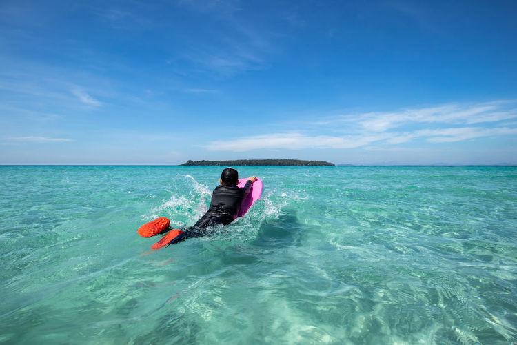 Boy surfboarding in sea against sky