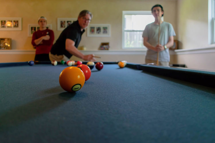 Men playing pool with sons at home