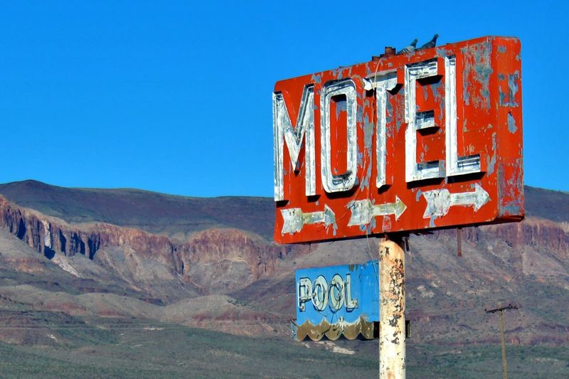 Pigeons roosting atop sign for an abandoned motel. Abandoned Arizona Birds Clear Sky Disrepair Distant Mountains Faded Hotel Juxtaposition Motel Motel Sign Mountains Nature Neon Old Pigeons Red Resting Retro Roosting Route 66 Sign Signage Signs Vintage