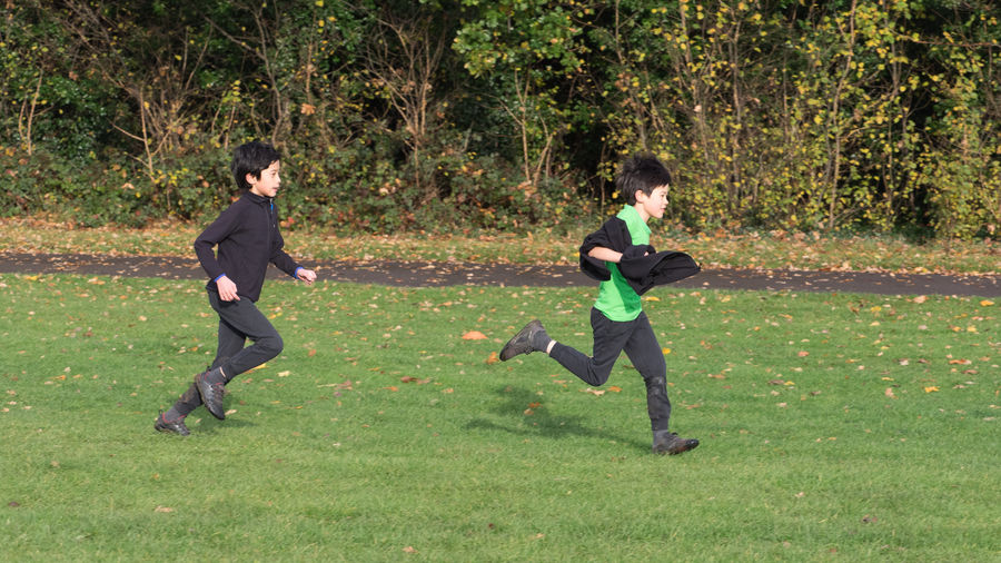 Side view of siblings running on grassy field