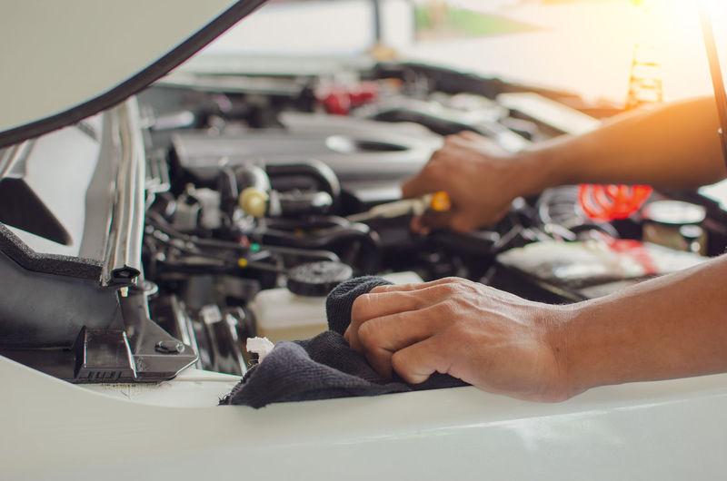 Cropped hands of mechanic repairing car in garage
