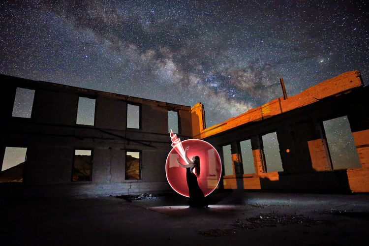 Digital composite image of man standing against building at night