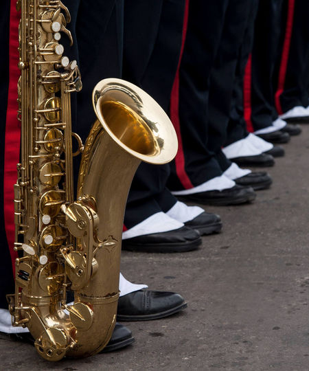Low section of marching band standing with saxophone on road