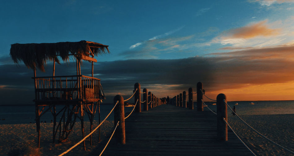 Pier amidst sea against sky during sunset
