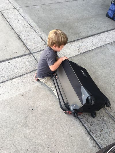 High angle view of boy with wheeled luggage on street