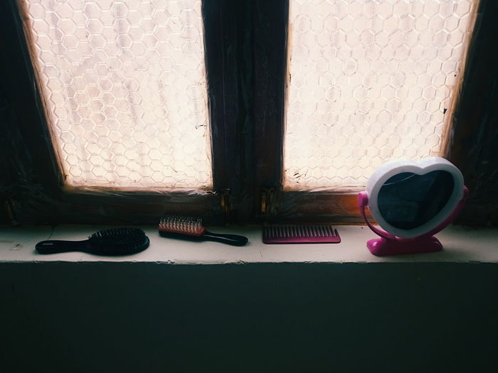 High angle view of combs and mirror on window sill