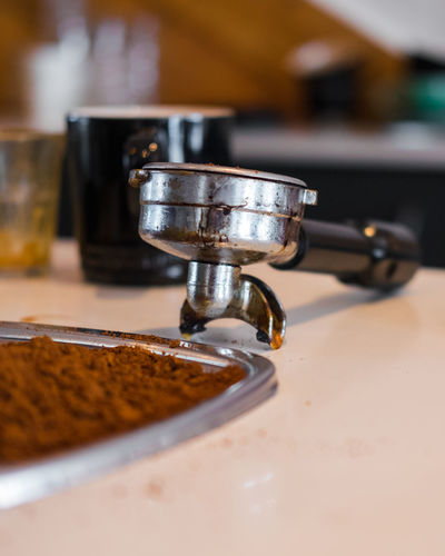 Close-Up Of Coffee And Porta Filter On Table In Kitchen