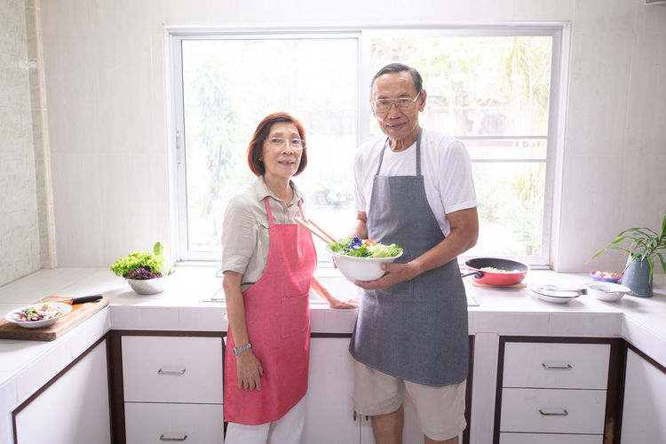 Portrait of smiling senior couple preparing food in kitchen