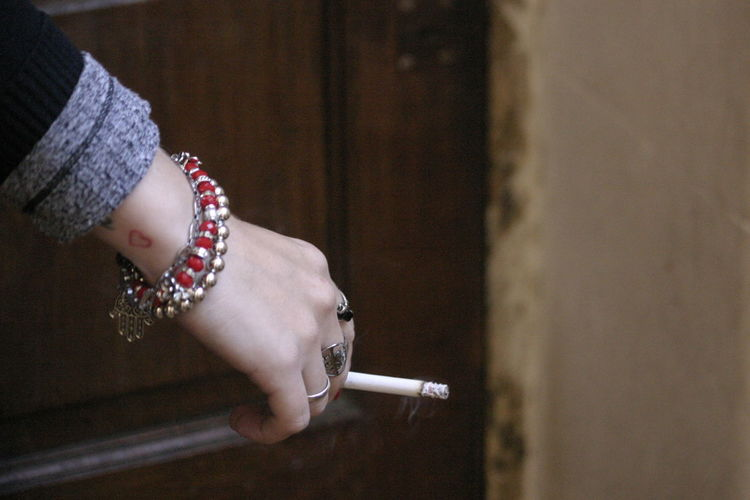 Cropped Hand Of Woman Holding Cigarette